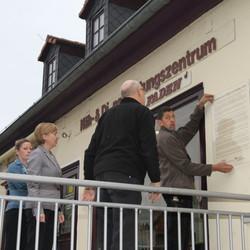Ortsbürgermeister Holger Fritzsche und die Mitarbeiter der Sparkasse Burgenlandkreis beratschlagen, wo die Tafel an der Fassade angebracht werden sollte.